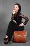 Porträt einer jungen attraktiven Frau, die auf einem Sitzpuff sitzt Stockfotografie