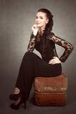 Porträt einer jungen attraktiven Frau, die auf einem Sitzpuff sitzt Stockfotos