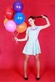 Porträt einer jungen attraktiven Frau, die Bündel von vielen brigh hält Stockfotos