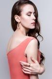 Porträt einer jungen attraktiven Frau im korallenroten Kleid und im goldenen Schmuck Stockfotografie