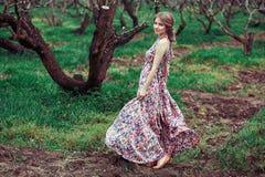 Porträt einer jungen blonden Frau auf einem Hintergrund von blühenden Bäumen Mädchen-Spinnen rosa Kleid, das im Wind flattert Stockfoto