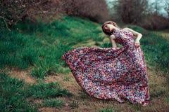 Porträt einer jungen blonden Frau auf einem Hintergrund von Frühlingsbäumen Mädchen-Spinnen rosa Kleid, das im Wind flattert Lizenzfreie Stockbilder