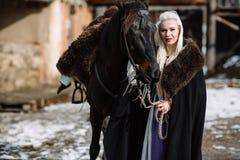 Porträt einer jungen blonden Frau in einem schwarzen Mantel mit einem Pferd Stockbild
