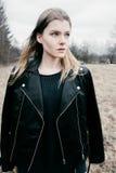Porträt einer jungen blonden Frau in einer schwarzen Jacke im Wald Stockfoto