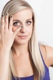 Porträt einer jungen blonden Frau mit der Hand auf ihrem Gesicht Lizenzfreies Stockbild