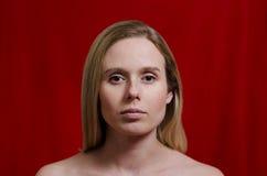 Porträt einer jungen Blondine auf rotem Hintergrund Lizenzfreies Stockbild