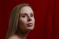 Porträt einer jungen Blondine auf rotem Hintergrund Stockfotos