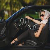 Porträt einer jungen Dame in einem schwarzen Kabriolett Lizenzfreies Stockbild