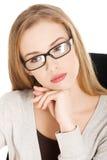 Porträt einer jungen durchdachten Frau in den Gläsern stockfoto