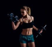 Porträt einer jungen Eignungsfrau in der Sportkleidung, die Training mit Dummköpfen auf schwarzem Hintergrund tut Gebräuntes sexy Stockfotos
