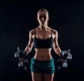 Porträt einer jungen Eignungsfrau in der Sportkleidung, die Training mit Dummköpfen auf schwarzem Hintergrund tut Gebräuntes sexy Lizenzfreie Stockfotos