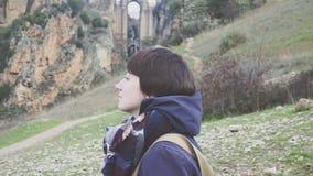 Porträt einer jungen Frau auf einem Hintergrund von einer Berglandschaft und von alten Stadt stock footage