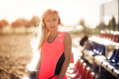 Porträt einer jungen Frau des Sitzes, die draußen nach erfolgreichem rüttelndem Training stillsteht Blonde tragende Sportkleidung Lizenzfreies Stockbild