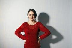 Porträt einer jungen Frau, die auf blauem Hintergrund mit der Handtaille steht stockfotografie