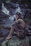 Porträt einer jungen Frau, die auf dem Felsen meditiert stockfotografie