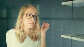 Porträt einer jungen Frau, die auf Gläsern versucht und sie annimmt stock footage
