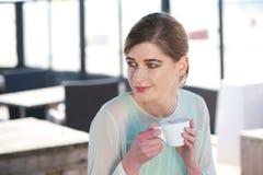 Porträt einer jungen Frau, die draußen einen Tasse Kaffee genießt Stockbilder