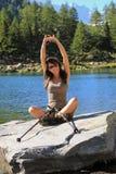 Porträt einer jungen Frau, die durch einen See ausdehnt stockfotografie