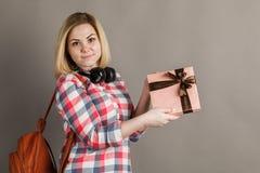 Porträt einer jungen Frau, die ein Geschenk hält Student in kariertem s lizenzfreie stockfotos