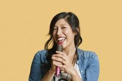Porträt einer jungen Frau, die in eine Haarbürste über farbigem Hintergrund singt Lizenzfreie Stockfotos