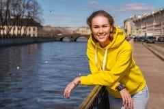 Porträt einer jungen Frau, die an einem sonnigen Tag auf einer Frühlingsstraße durch den Fluss lächelt lizenzfreie stockfotografie