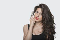 Porträt einer jungen Frau, die Handy über grauem Hintergrund verwendet Lizenzfreies Stockbild