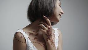 Porträt einer jungen Frau, die Hennastrauchmalerei auf ihrem Körper demonstriert stock video