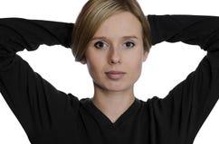Porträt einer jungen Frau, die ihr Haar oben auf weißem Hintergrund anhält Stockbild
