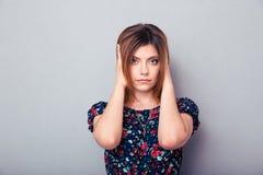 Porträt einer jungen Frau, die ihre Ohren bedeckt lizenzfreie stockbilder