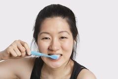 Porträt einer jungen Frau, die ihre Zähne über hellgrauem Hintergrund putzt Stockfotos