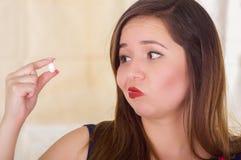 Porträt einer jungen Frau, die in ihrer Hand eine vaginale Tablette der weichen Gelatine oder ein Zäpfchen, Behandlung von Krankh Stockfotografie