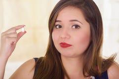 Porträt einer jungen Frau, die in ihrer Hand eine vaginale Tablette der weichen Gelatine oder ein Zäpfchen, Behandlung von Krankh Lizenzfreie Stockfotografie