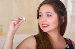 Porträt einer jungen Frau, die in ihrer Hand eine vaginale Tablette der weichen Gelatine oder ein Zäpfchen, Behandlung von Krankh Lizenzfreie Stockfotos