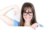 Porträt einer jungen Frau, die leerem Raum ay leeres Brett zeigt Lizenzfreie Stockfotos