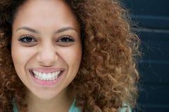 Porträt einer jungen Frau, die mit glücklichem Ausdruck auf Gesicht lächelt Lizenzfreies Stockbild