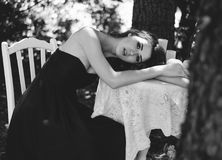 Porträt einer jungen Frau in einem langen Abendkleid, sitzt sie an einem Tisch im Wald Mädchen versteckt sich im Hemd eines Manne Stockbilder