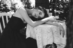 Porträt einer jungen Frau in einem langen Abendkleid, sitzt sie an einem Tisch im Wald Mädchen versteckt sich im Hemd eines Manne Lizenzfreie Stockfotos