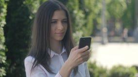 Porträt einer jungen Frau in einem weißen Hemd benutzt einen Smartphone im Nachmittag auf einer Straße in der Stadt stock video footage