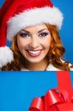Porträt einer jungen Frau in einem Winterhut, der ein Geschenk hält Lizenzfreie Stockfotos