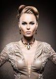 Porträt einer jungen Frau im Make-up und im Schmuck Stockbild