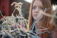 Porträt einer jungen Frau im Winter im Garten auf Roheisenzaun mit Frost Hoarfrost stockfoto