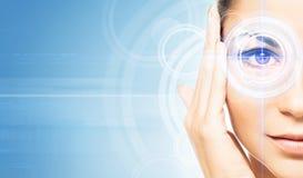 Porträt einer jungen Frau mit einem Laser auf ihrem Auge stockbild