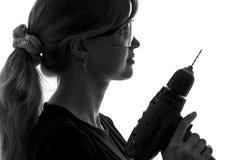 Porträt einer jungen Frau mit einer elektrischen Bohrmaschine Stockbilder