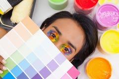 Porträt einer jungen Frau mit Farbenproben Stockbild