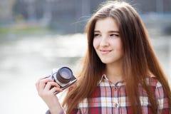 Porträt einer jungen Frau mit Fotokamera Stockfotografie