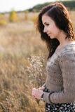Porträt einer jungen Frau mit Herbstblumenstrauß Stockfotografie