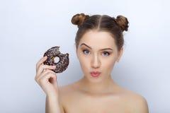 Porträt einer jungen Frau mit lustiger Frisur und bloßer Schultertat der Affe gegen weißen Studiohintergrund mit Schokoladendonut Stockfoto