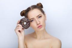 Porträt einer jungen Frau mit lustiger Frisur und bloßer Schultertat der Affe gegen weißen Studiohintergrund mit Schokoladendonut Stockbild