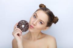 Porträt einer jungen Frau mit lustiger Frisur und bloßer Schultertat der Affe gegen weißen Studiohintergrund mit Schokoladendonut Stockfotos