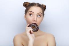 Porträt einer jungen Frau mit lustiger Frisur und bloßer Schultertat der Affe gegen weißen Studiohintergrund mit Schokoladendonut Stockbilder